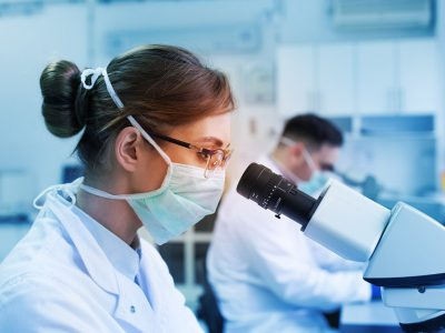 Lab technicians wear PPE while remaining socially-distant.